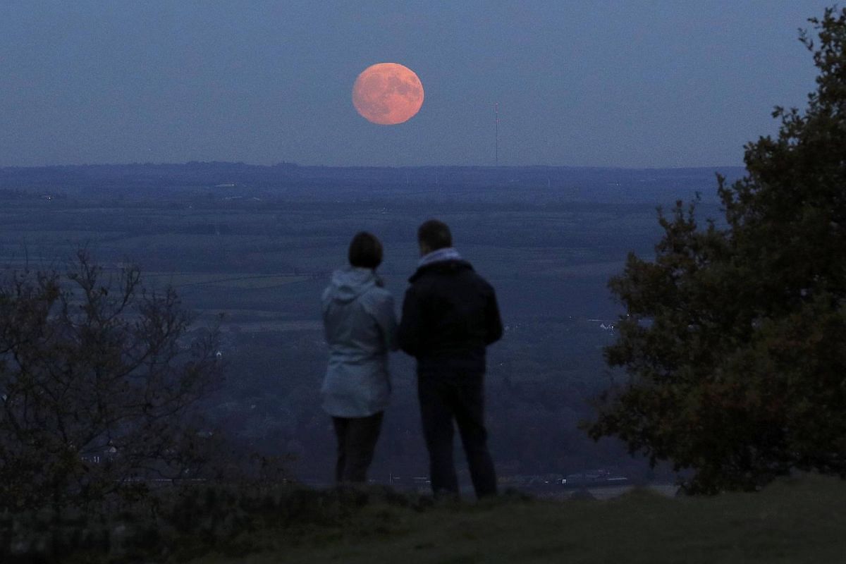 A couple watching the moon rise a day before the 'supermoon' spectacle on Beacon Hill near Loughborough, Britain, on Nov 13, 2016.