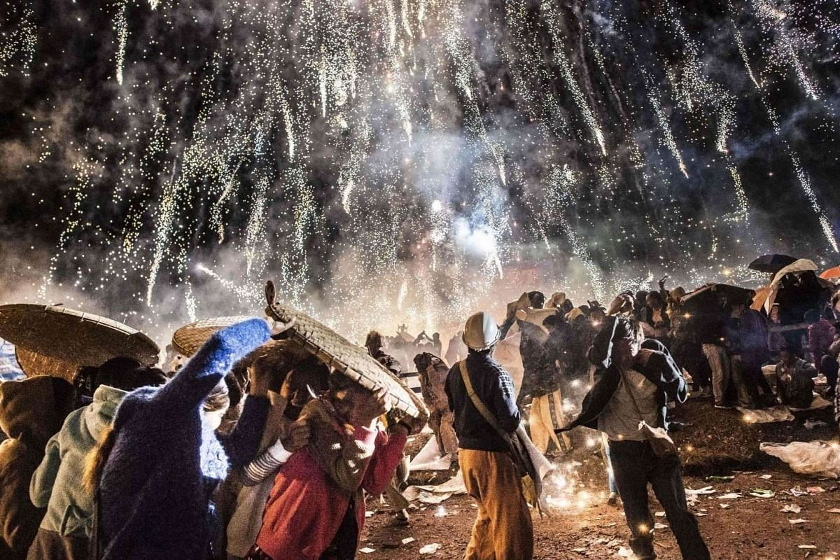 People protecting themselves from fireworks, being carried by a hot air balloon, that ignited before the balloon was at a sufficient height during the Tazaungdaing Lighting Festival at Taunggyi in Myanmar's north-eastern Shan State.
