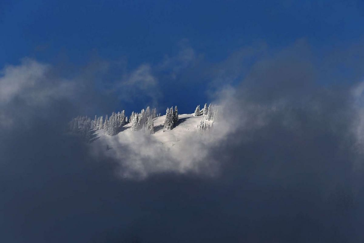 A snow covered mountain is seen behind clouds near Balderschwang, southern Germany, on Nov 12, 2016.