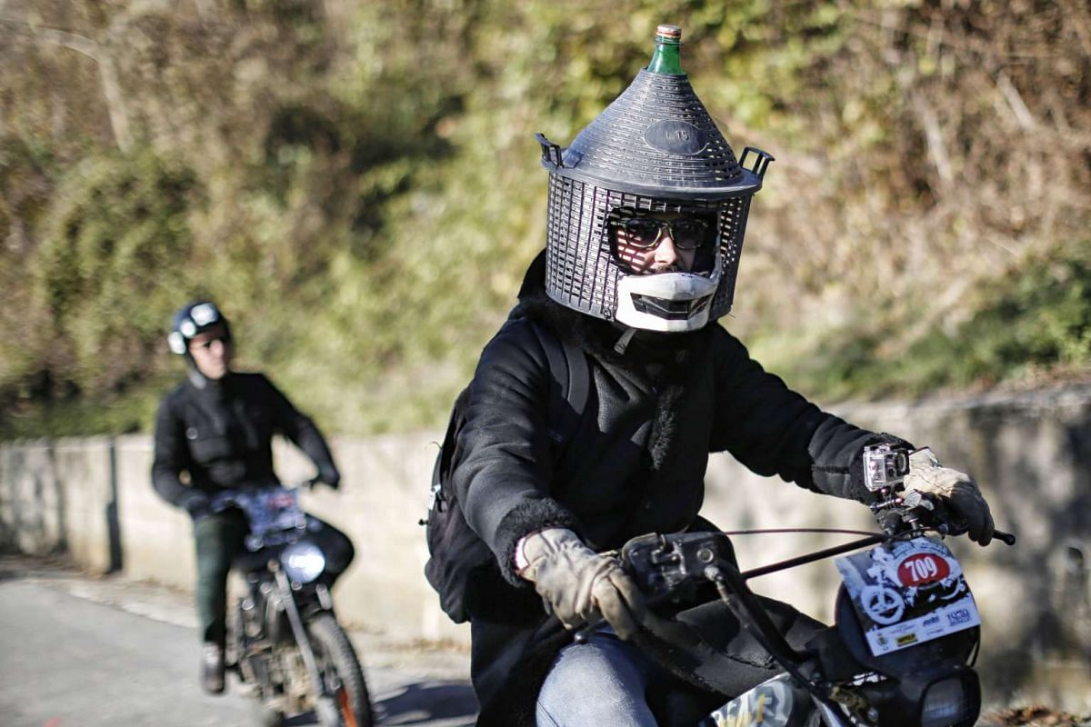 """People taking part in the """"Monferraglia"""" event during which people ride old single speed motors in Ceva, near Cuneo, northern Italy, on Nov 13, 2016."""