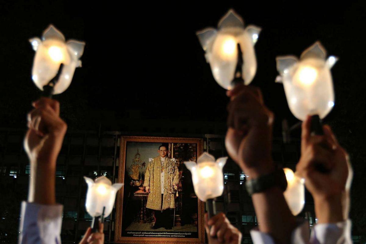 Thai mourners holding up candles in front of a large portrait of the late Thai King Bhumibol Adulyadej on a building at Siriraj Hospital in Bangkok, Thailand, on Nov 13, 2016.