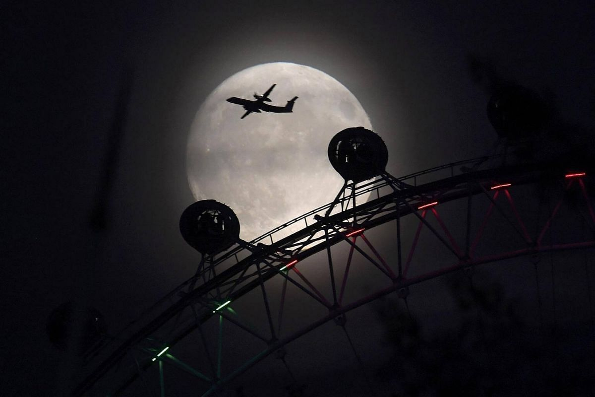 An aeroplane flying past the London Eye wheel, and moon, a day before the 'supermoon' spectacle in London on Nov 13, 2016.