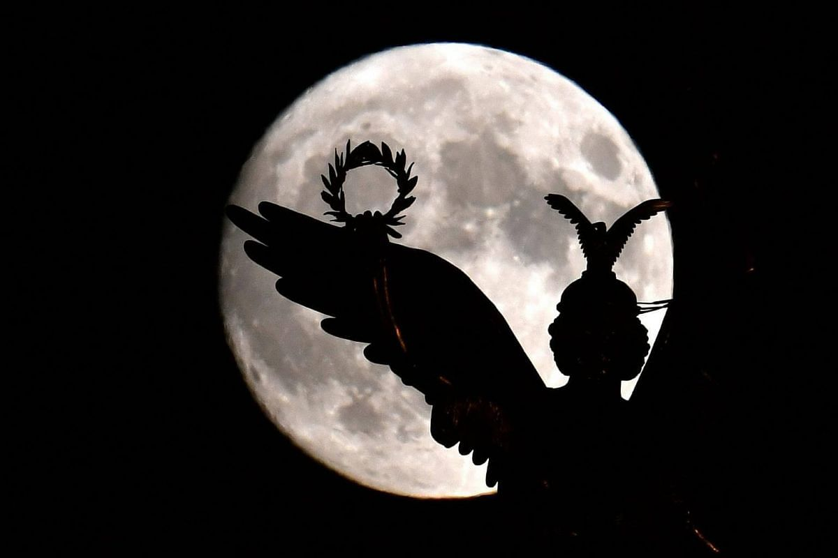 The figure of Viktoria with her laurel wreath on the victory column against the full moon in Berlin, Germany, on Nov 13, 2016.
