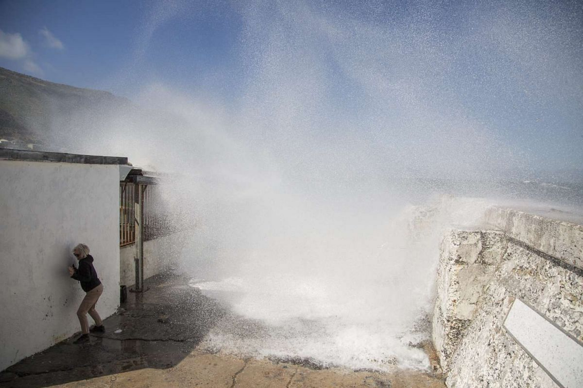 A woman runs from waves break over the Kalk Bay Harbour wall in Cape Town, South Africa, November 14, 2016. PHOTO: EPA