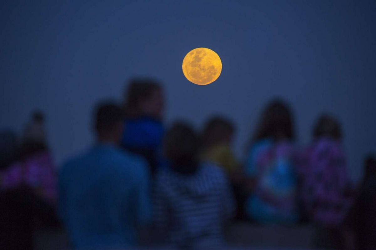 South African families watch the supermoon rise over the Cedarberg Mountains in Cape Town.