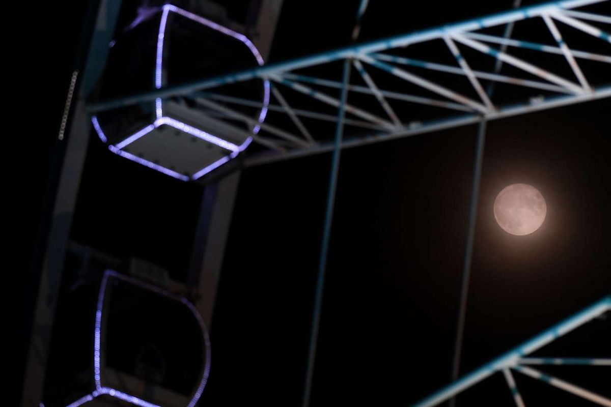 The supermoon is pictured beyond the capsules of the Liverpool Wheel, a ferris wheel in Liverpool, north-west England, on Nov 14, 2016.