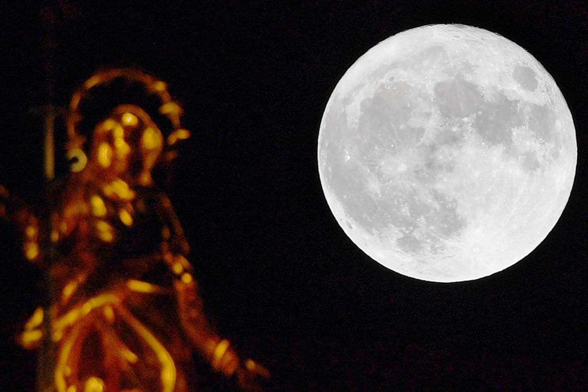 The full moon rising over Milan's Duomo in Italy.