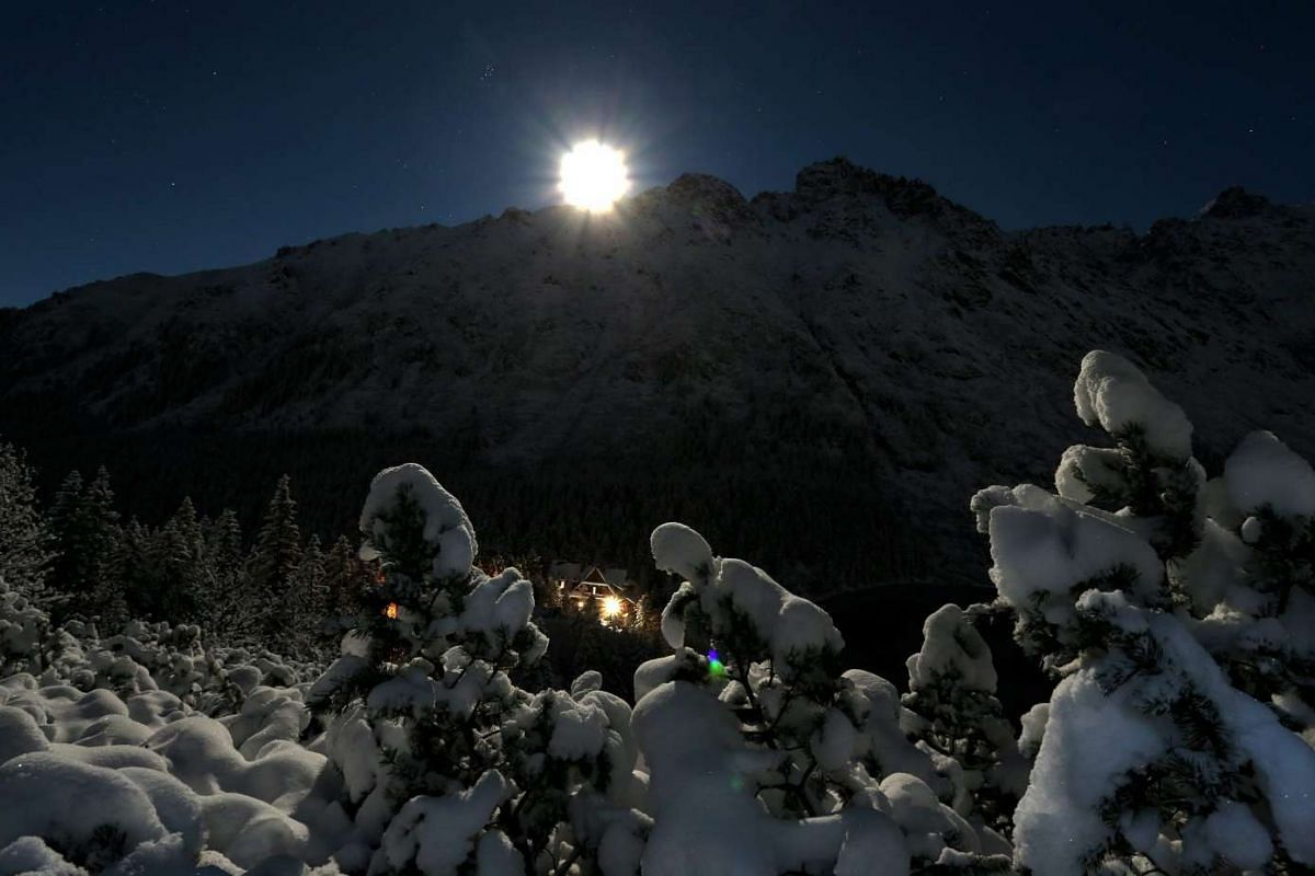 The supermoon rises over Zabi Szczyt peak in the Tatra Mountains near Zakopane, Poland.