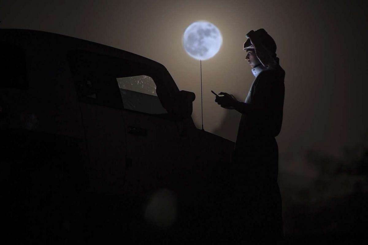 A man looks at his phone as a supermoon rises over the desert near Tabuk, north-west of the Saudi capital Riyadh.