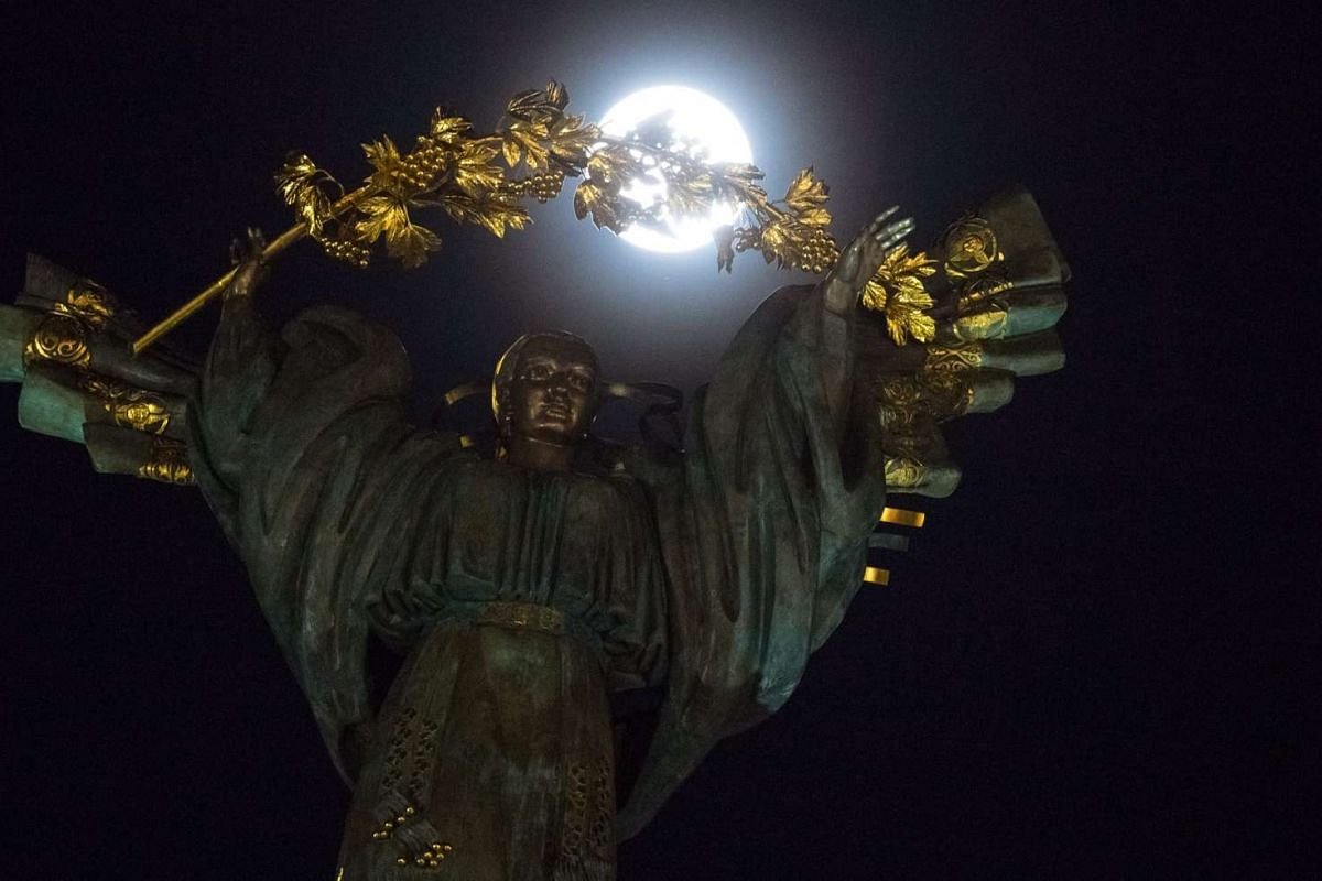 The supermoon rises behind the statue of Goddess Bereginya at the Independence Square in Kiev, Ukraine.