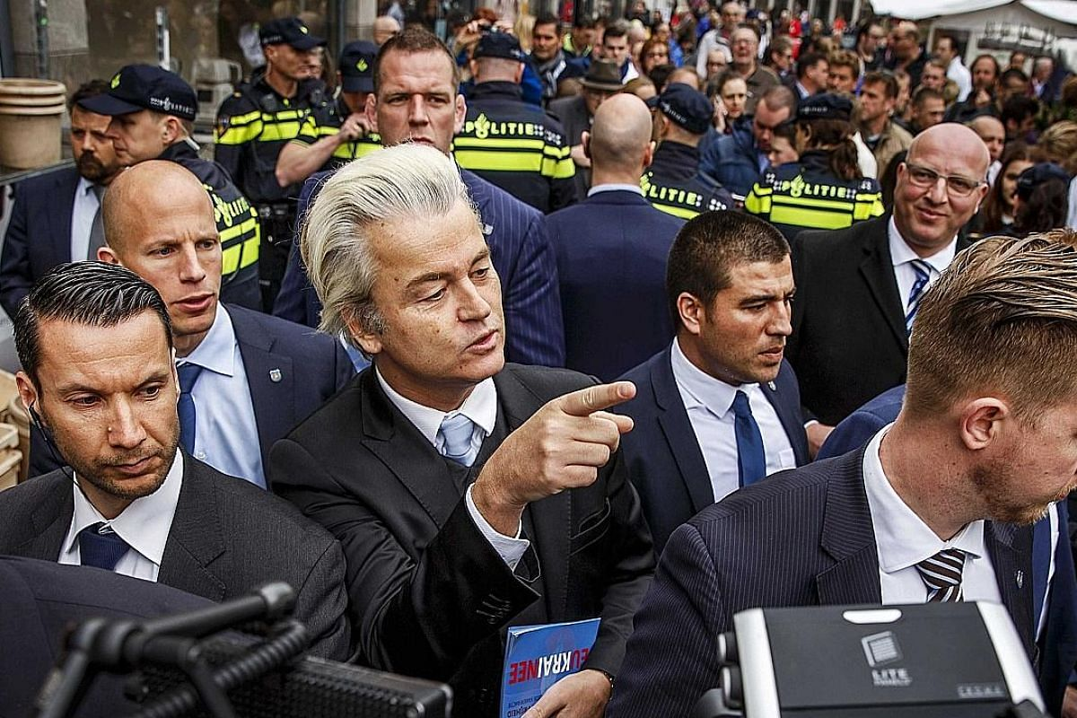 Above: Dutch right-wing politician Geert Wilders, known for his tirades against Islam and immigration, has hailed the shock result of the US election. Right: An Italian trade union member, with a copy of the country's Constitution, at a strike protes
