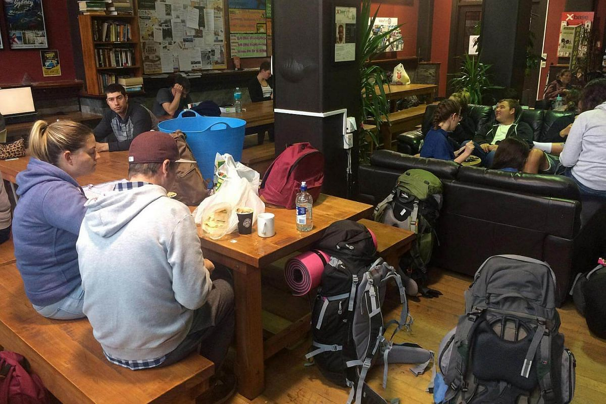 Travellers at the Base backpackers hostel in Wellington eat while waiting to leave the city, on Nov 15, 2016 after the New Zealand earthquake disrupted the travel plans of many across the country.