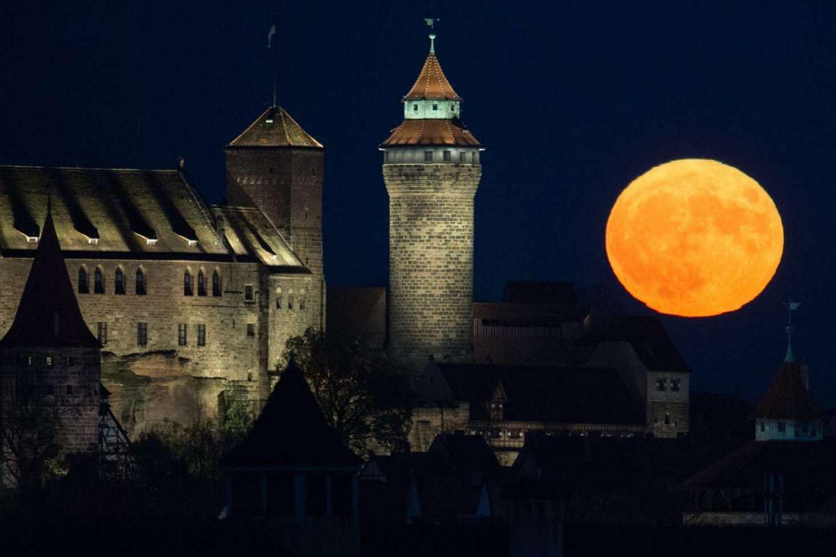 The full moon rises behind the Kaiserburg castle in Nuremberg, Germany, on Nov 14, 2016.