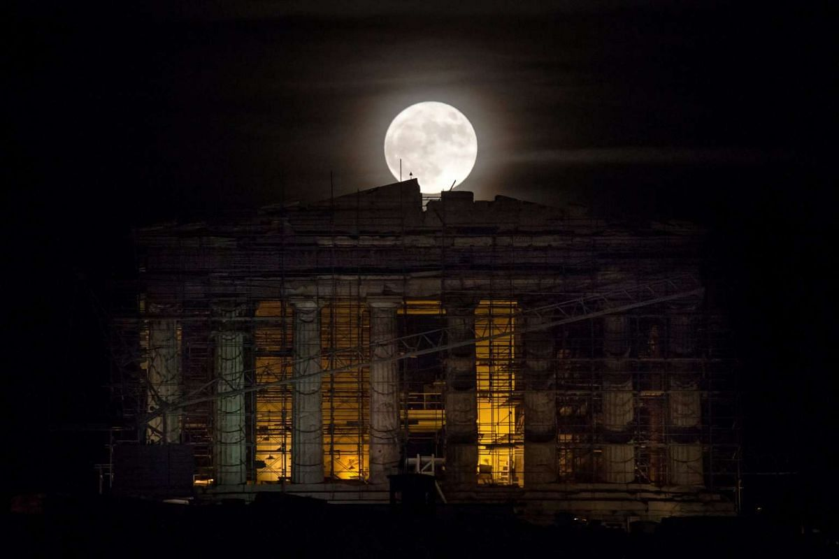 A rising supermoon is seen over the Parthenon temple atop the ancient Acropolis hill in Athens, Greece, on Nov 14, 2016.