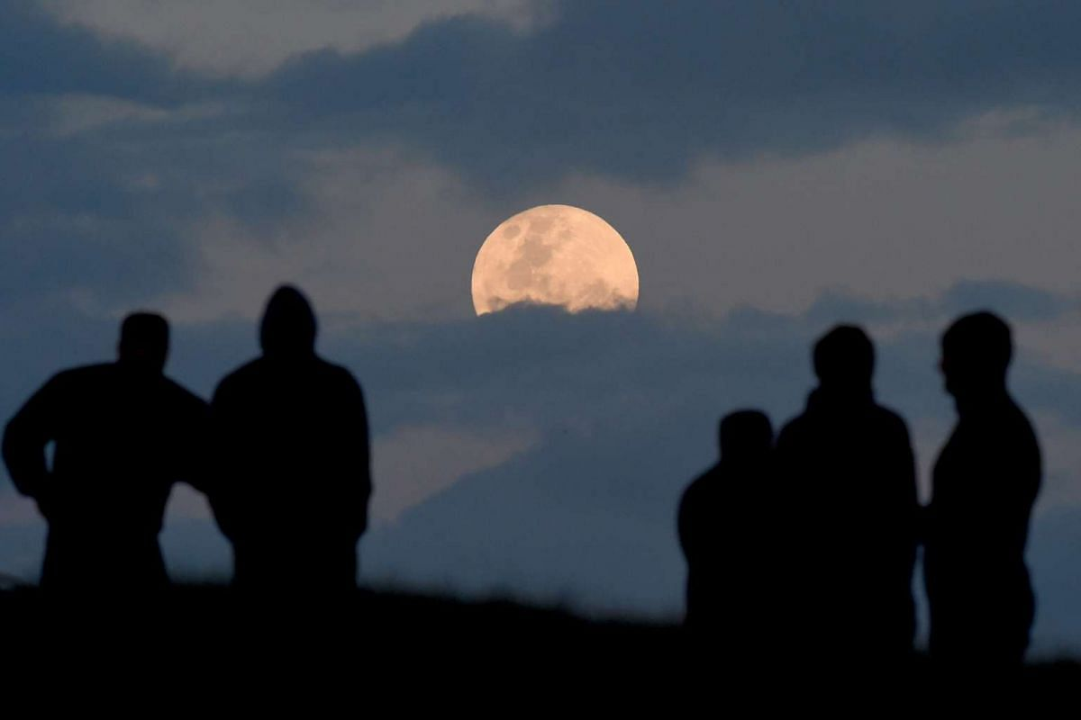 A crowd watches the full moon between the clouds from Balg Hill south of Sydney, Australia, on Nov 14, 2016.