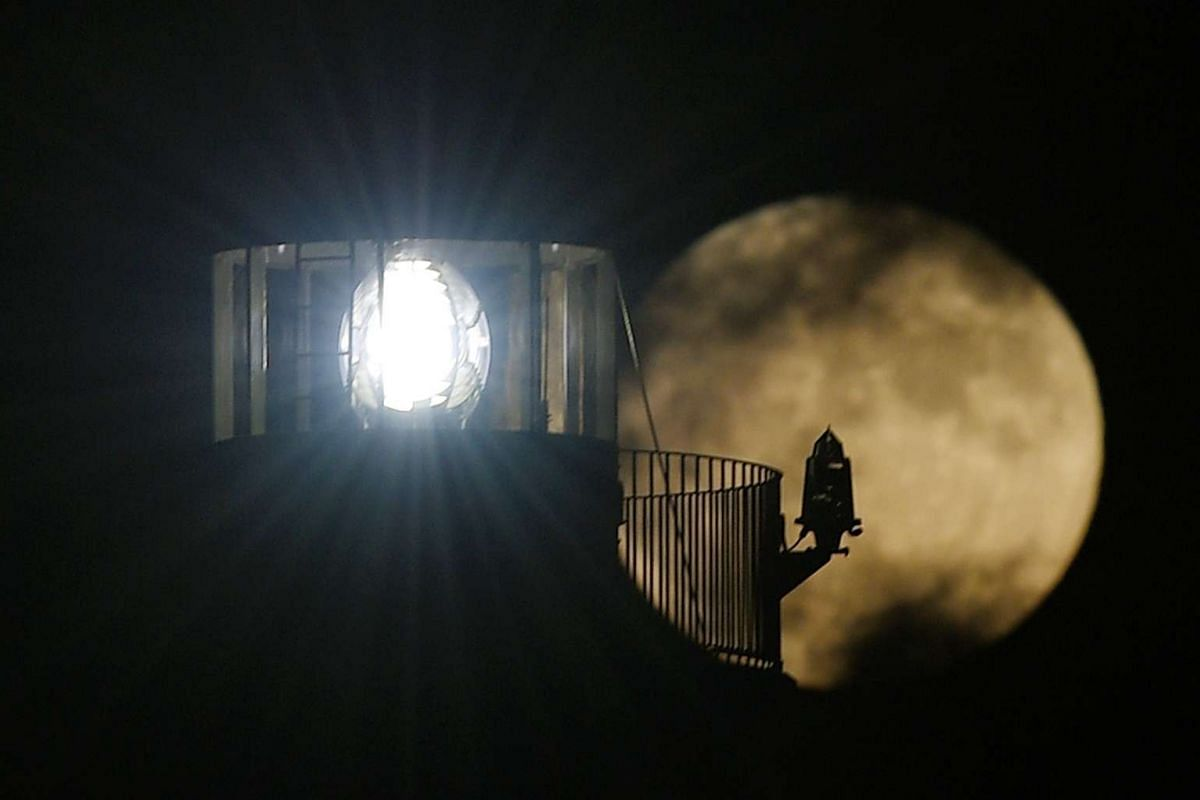 A supermoon rises behind a lighthouse in Vilanova i la Geltru near Barcelona, Spain, on Nov 14, 2016.