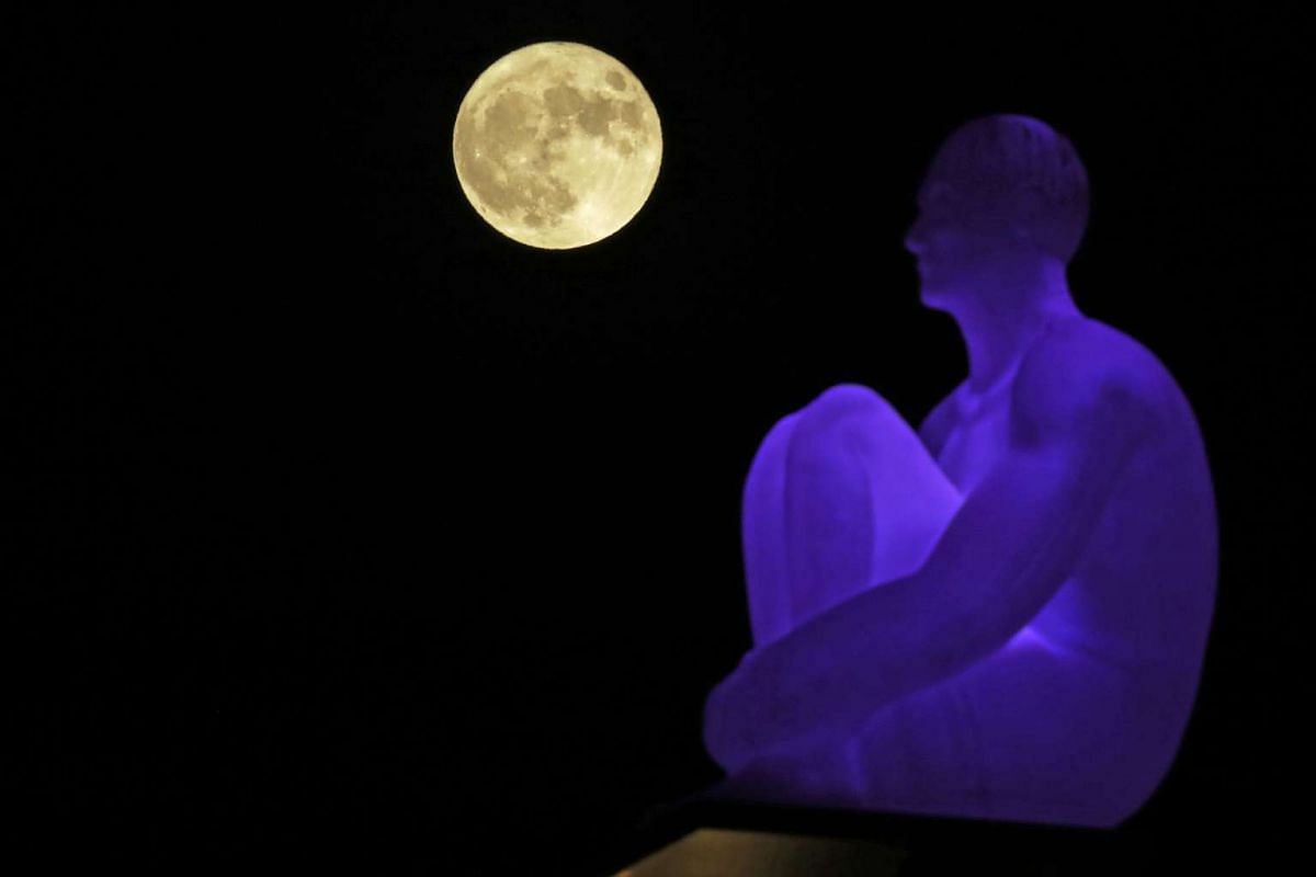 The supermoon rises behind one of the seven statues by Spanish artist Jaume Plensa on Massena square in Nice, France, on Nov 14, 2016.