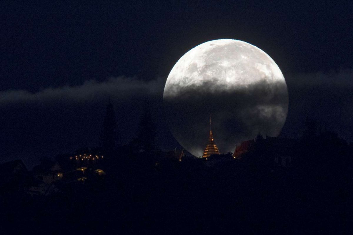 The supermoon is partly covered by clouds as it sets behind Wat Phrathat Doi Suthep in the northern capital of Chiang Mai, Thailand, on Nov 15, 2016.