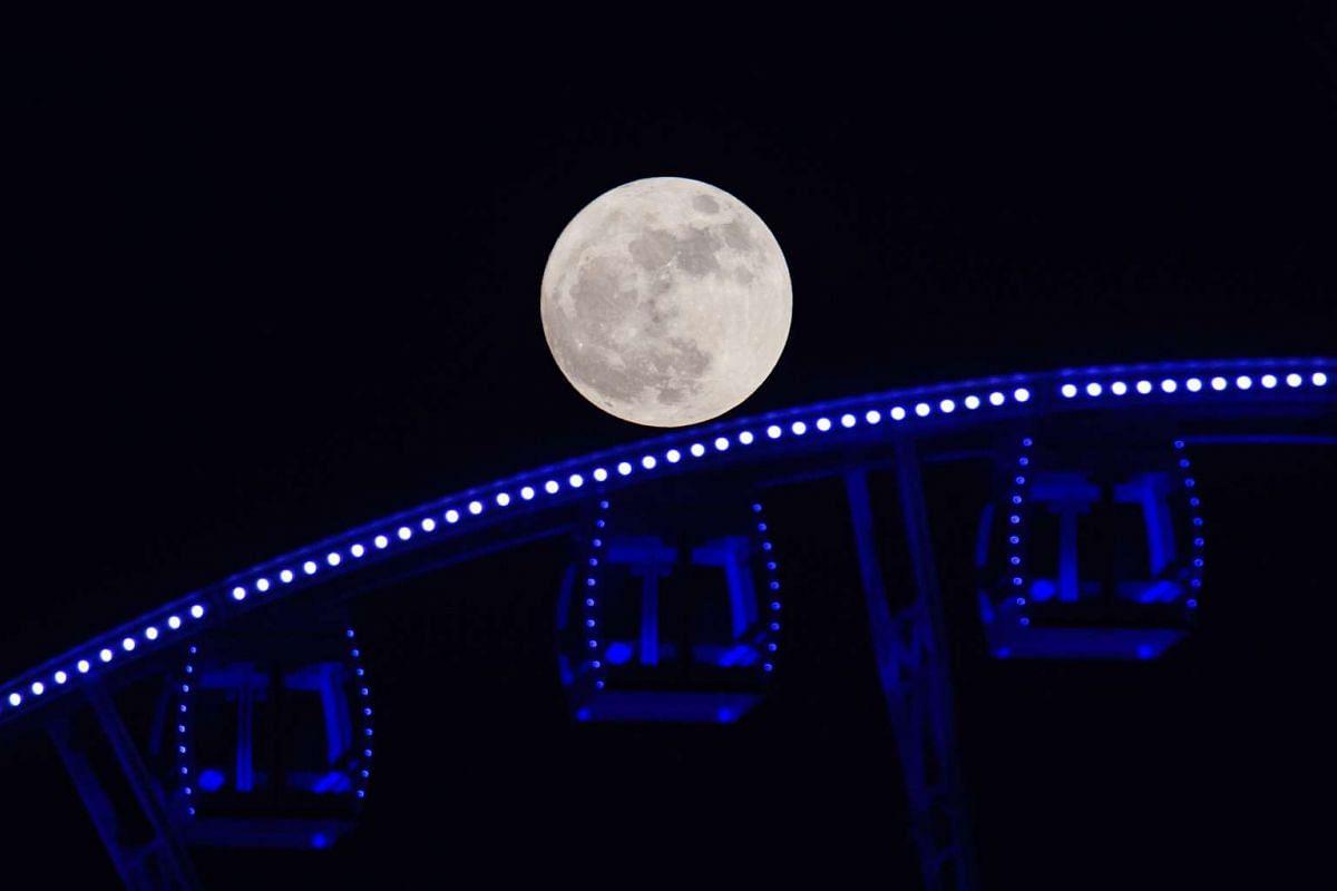 A supermoon is seen rising beyond a ferris wheel in Hong Kong on Nov 14, 2016.