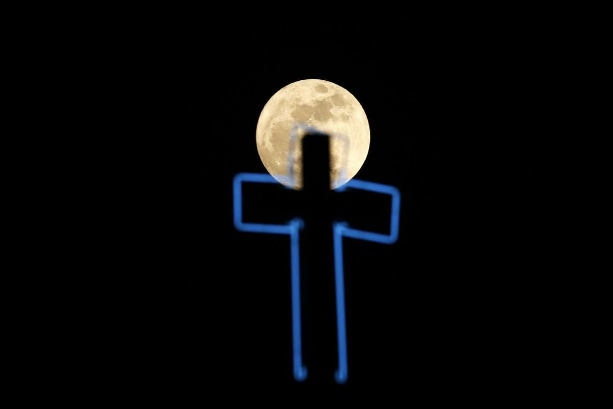 The moon rises over a Catholic church tower in Manila, Philippines, on Nov 14, 2016.
