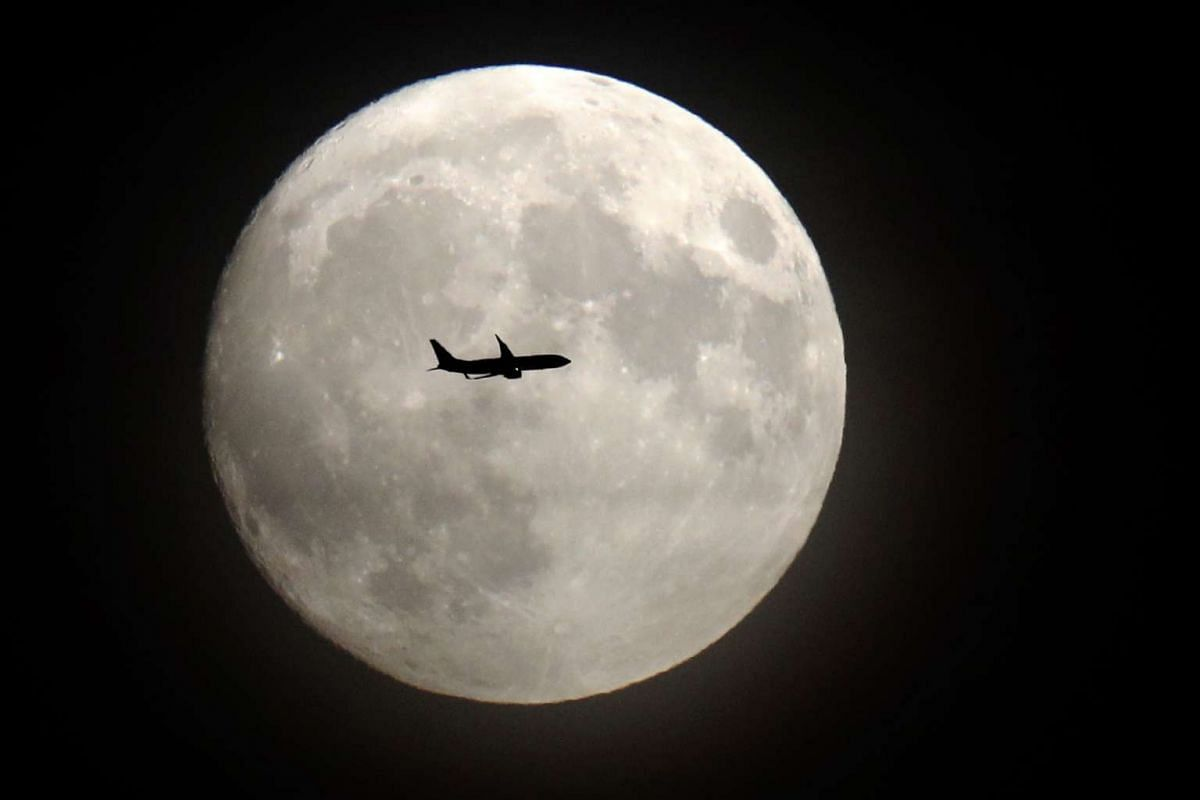 A commercial jet flying past the moon on its approach to Heathrow airport in west London on Nov 13, 2016.