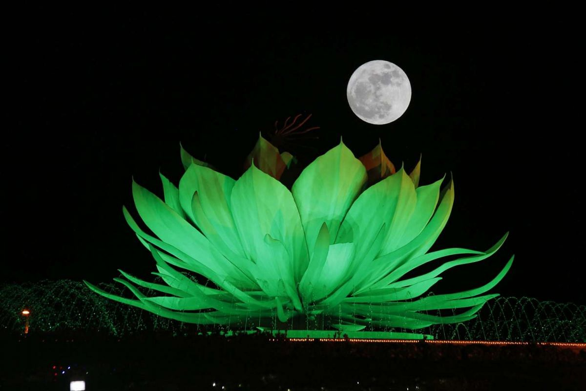 The moon rises over the Lotus roundabout in Naypyitaw, Myanmar, on Nov 14, 2016.