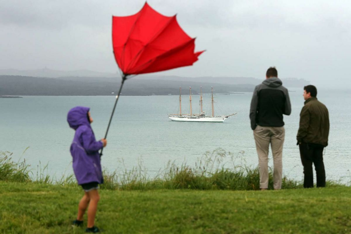 A child struggles with an umbrella as people watch the Bach Esmerelda from Chile arrive into the Waitemata Harbour as part of the fleet entry to celebrate the Royal New Zealand Navy's 75th anniversary in Auckland on November 16, 2016. PHOTO: AFP