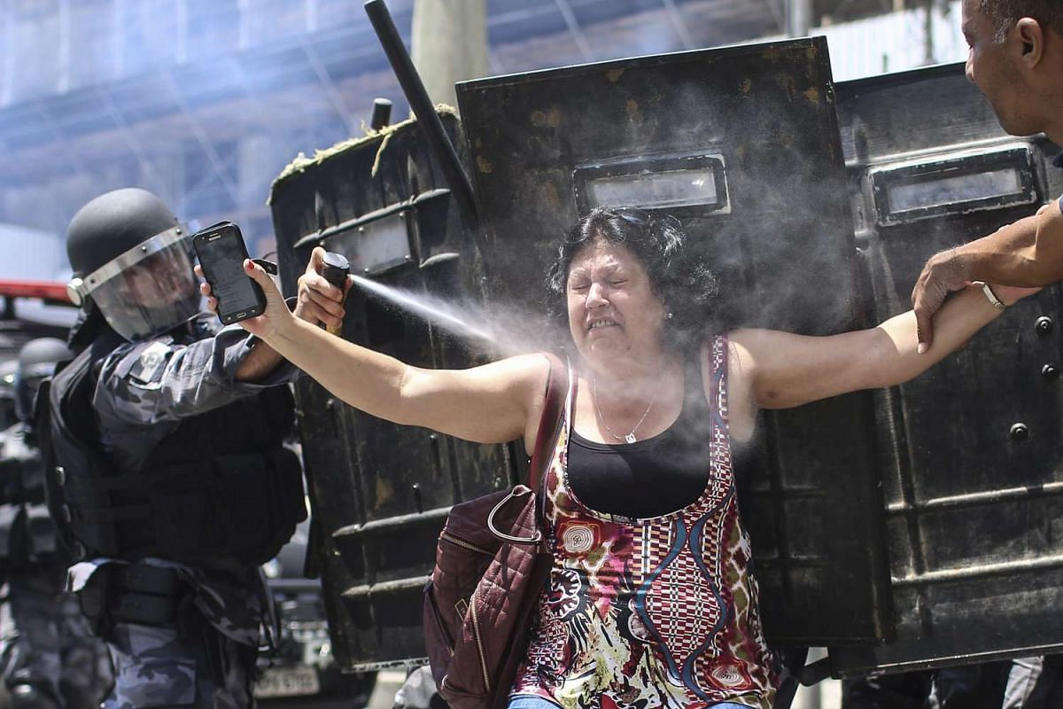 A Brazilan policeman sprays tear gas at a demonstrator during a protest against the Government's austerity measures for public officials at the headquarter of Legislative Assembly in Rio de Janeiro, Brazil, November 16, 2016. PHOTO: EPA