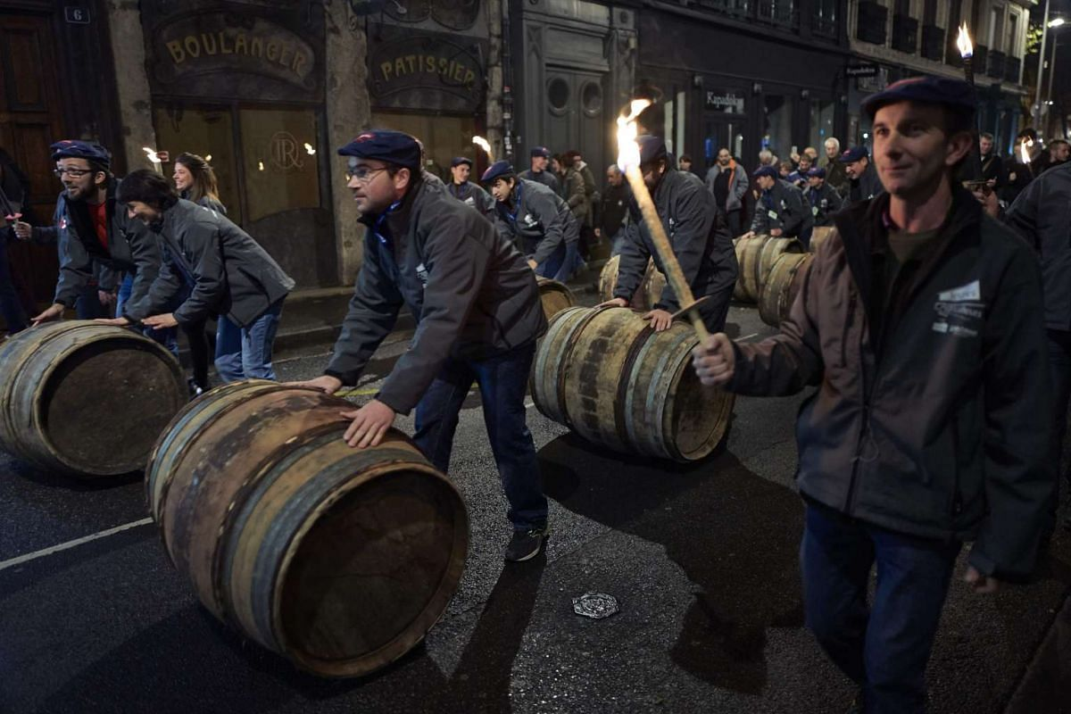 Barrels of Beaujolais Nouveau wine are rolled by wine-growers on November 17, 2016 in the streets of Lyon, France, during the official launch of the Beaujolais Nouveau. PHOTO: AFP