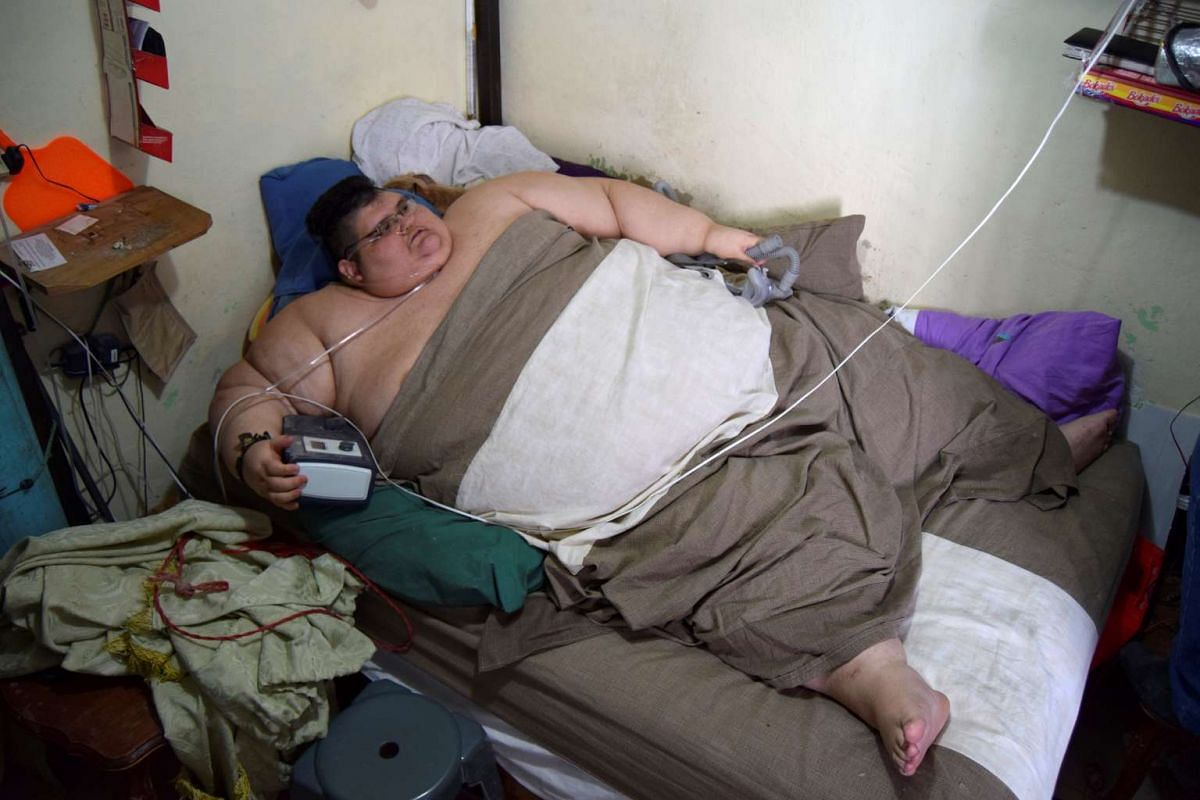 A photo released on November 17, 2016 shows Juan Pedro, lying in his bed at home as he waits for paramedics to transport him to a hospital in Guadalajara, to undergo treatment in order to shed excess from his 500-kilo weight, in Aguascalientes, Mexic