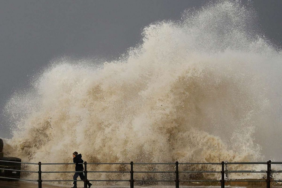 A woman is battered by a wave as she walks along the seafront in New Brighton, northern England November 16, 2016. PHOTO: REUTERS