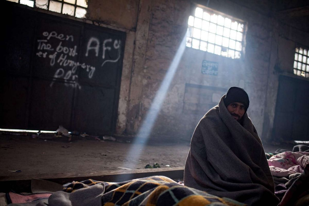 A Pakistani migrant sits in a makeshift shelter in an abandoned warehouse in Belgrade on November 16, 2016. PHOTO: AFP