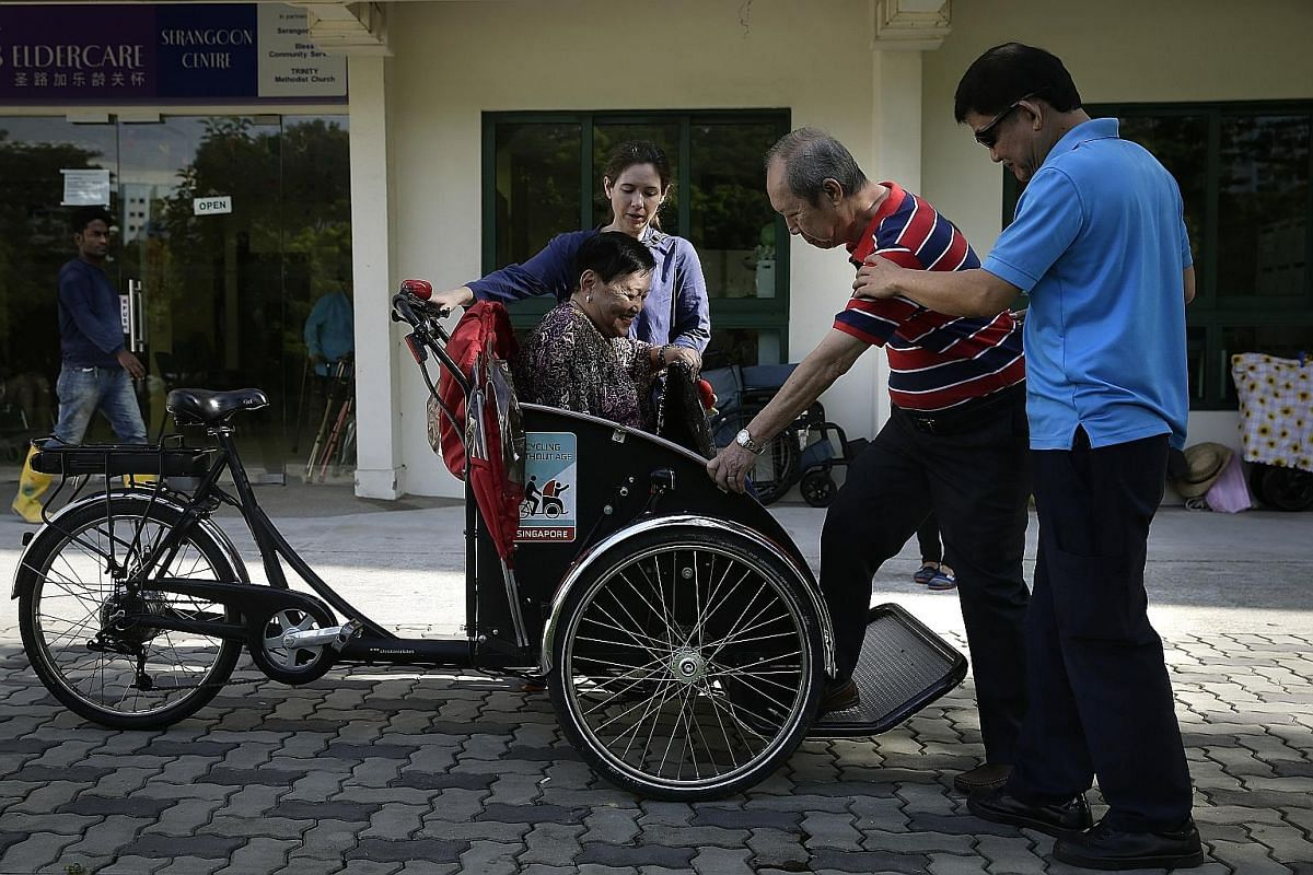 St Luke's ElderCare Centre staff member Bernard Khoo (right), 54, helping Mr Philip Lee, 79, and Ms Mary Tong, 70, into the trishaw on Oct 28. The trishaw has a low mount for easy access and was made with seniors in mind. With them is Ms Bussone, who deli