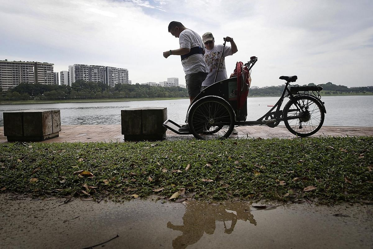 Above: Ms Nancy Chew, 45, helping her husband William Tan, 46, off the trishaw during a ride at Bedok Reservoir on Oct 29. Mr Tan is paralysed on the left side of his body after a stroke five years ago. His wife said the ride brought back memories of how