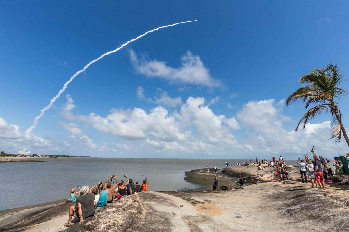 People take photos as an Ariane 5 space rocket with a payload of four Galileo satellites lifts off from ESA's European Spaceport in Kourou, French Guiana, on November 17, 2016. PHOTO: AFP