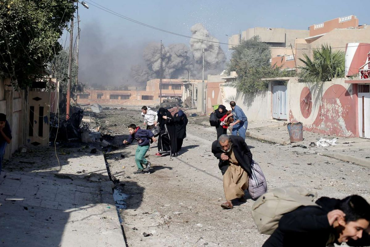 People run in panic after a coalition airstrike hit Islamic State fighters positions in Tahrir neighbourhood of Mosul, Iraq, November 17, 2016. PHOTO: REUTERS
