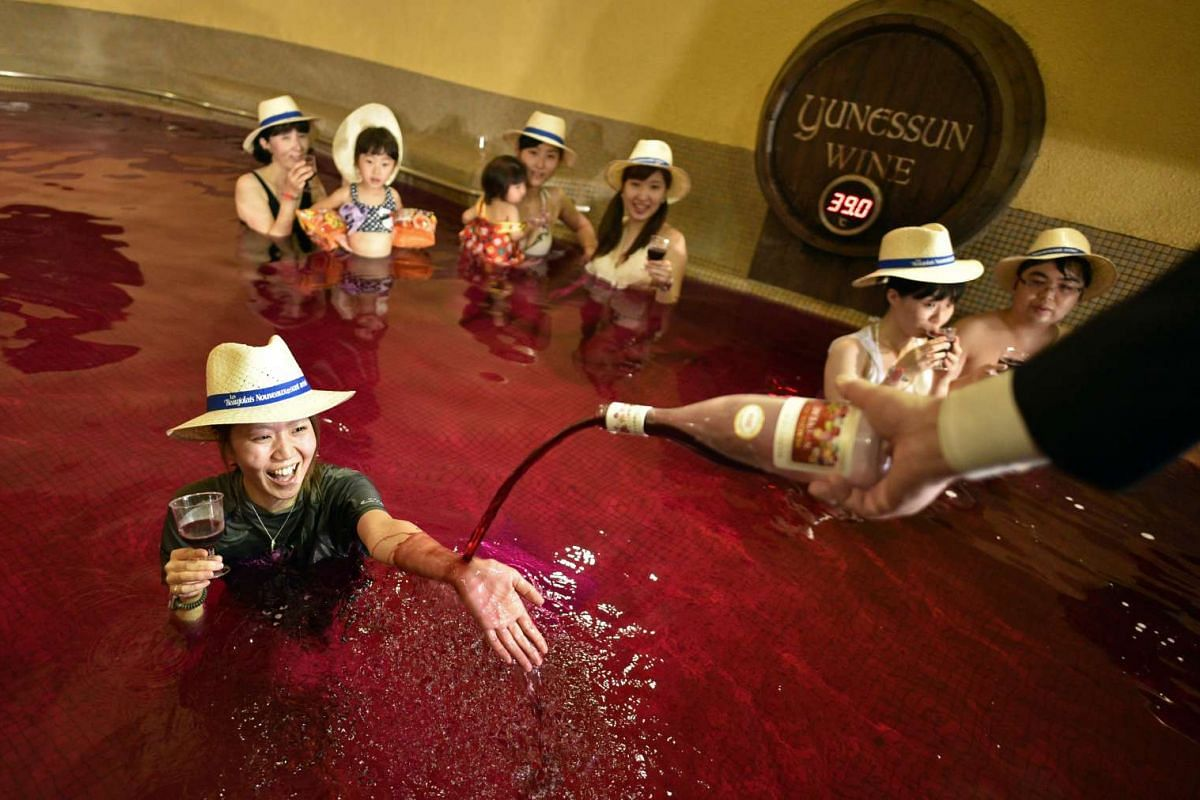 A man pours 2016 Beaujolais Nouveau wine on the hand of a woman in a colored hot water 'wine bath' at Hakone Kowakien Yunessun hot spring resort in Hakone, Kanagawa prefecture, west of Tokyo, Japan, November 17, 2016, on the day of the official relea