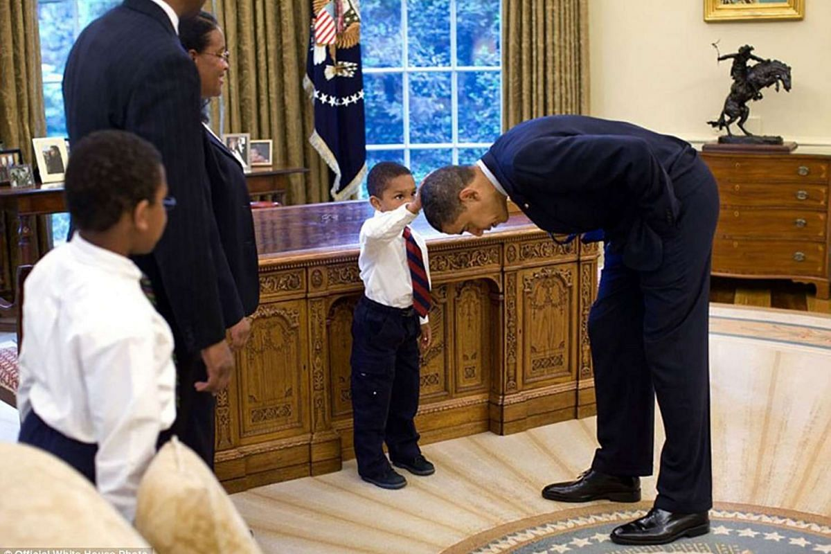 President Barack Obama bends over so the son of a White House staff member can pat his head during a family visit to the Oval Office on May 8, 2009.