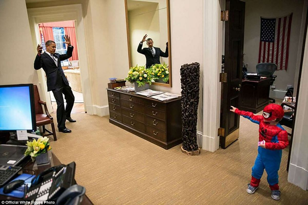 President Barack Obama lifts his arms in a the air as he pretends to be caught in Spider-Man's web as he greets the son of a White House staffer in the Outer Oval Office on Oct 26, 2012.