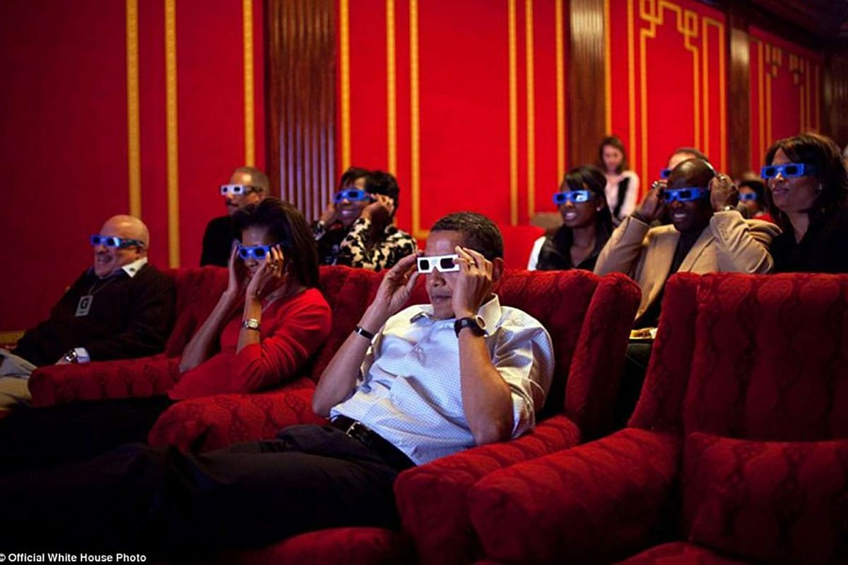 President Barack Obama holds 3-D glasses while watching the Super Bowl game at a Super Bowl Party in the family theater of the White House. Feb 1, 2009.