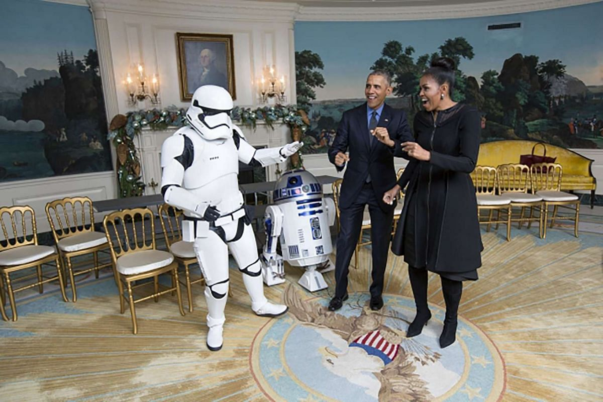President Barack Obama and First Lady Michelle Obama dance with a stormtrooper and R2-D2 from Star Wars in the Diplomatic Reception Room of the White House on Dec 18, 2015.