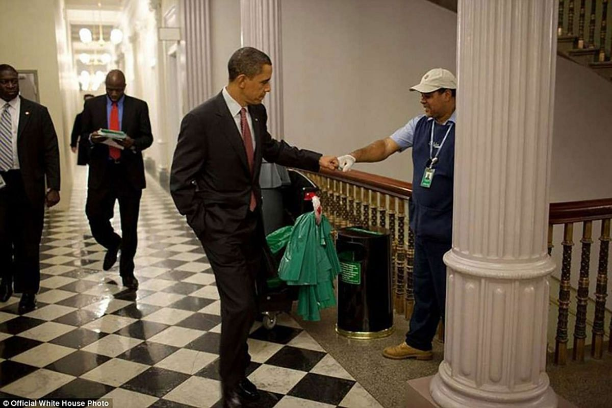 President Barack Obama fist-bumps custodian Lawrence Lipscomb in the Eisenhower Executive Office Building following the opening session of the White House Forum on Jobs and Economic Growth on Dec 3, 2009.