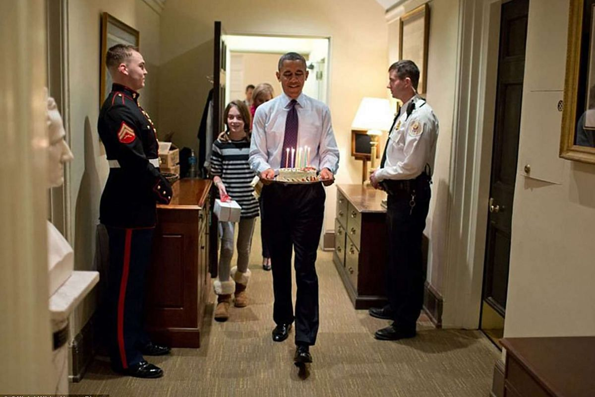 President Barack Obama, along with Chief of Staff Denis McDonough's daughter, carries a birthday cake to surprise McDonough in his West Wing office on Dec 2, 2013.