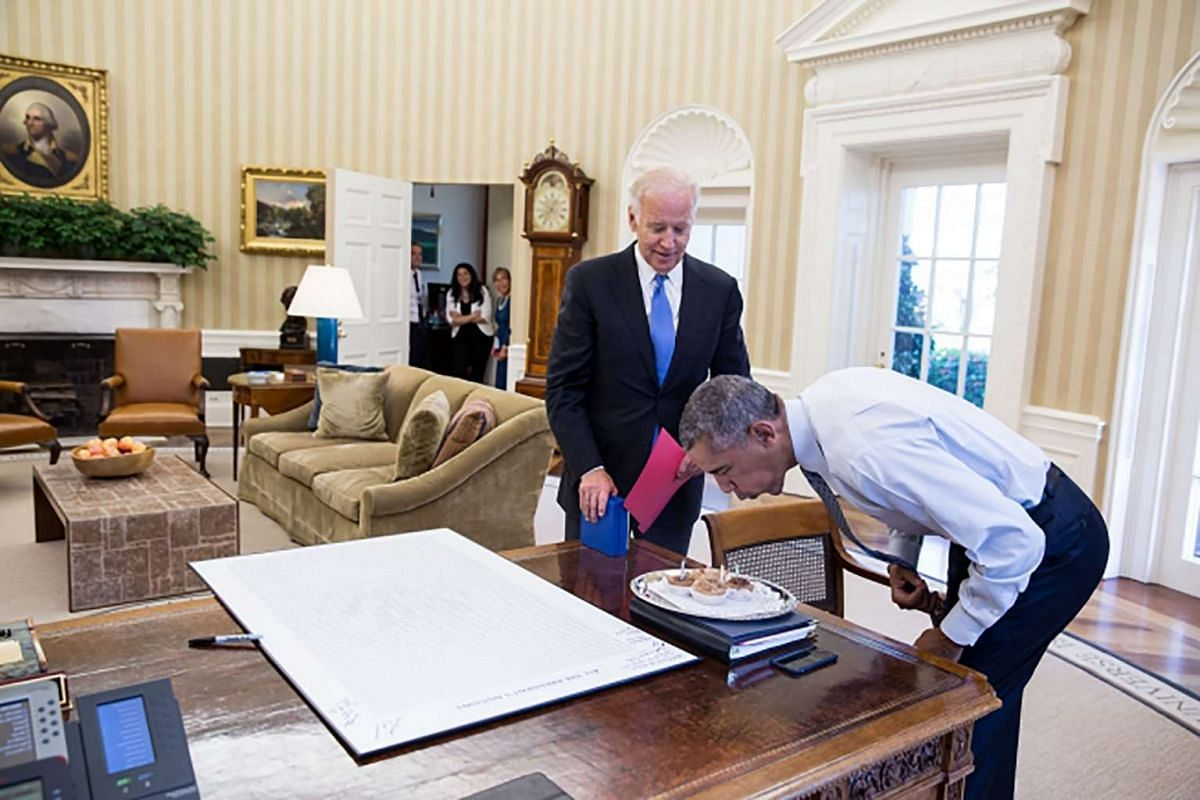 President Barack Obama blows out candles on birthday cupcakes brought to him by Vice President Joe Biden in the Oval Office on Aug 4, 2016.