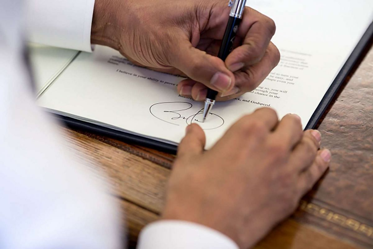 President Barack Obama signs commutation letters in the Oval Office, March 31, 2015. The President granted commutations for 22 individuals.