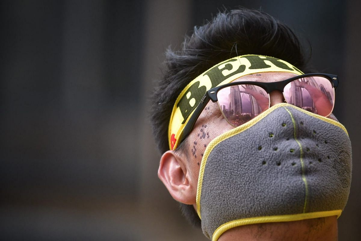 The KLCC is reflected in a protester's sunglasses as he stands on a road divider at the Bersih rally on Saturday (Nov 19).