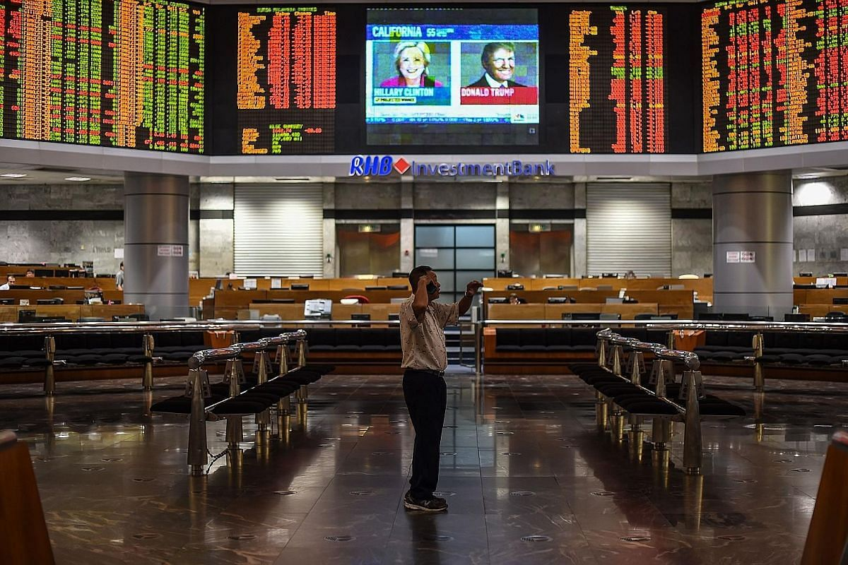 A trader reacting as electronic boards showed stock movements during the final day of the US presidential election at a private stock exchange in Kuala Lumpur on Nov 9. Share markets collapsed when Mr Trump looked set to win the race for the White Ho