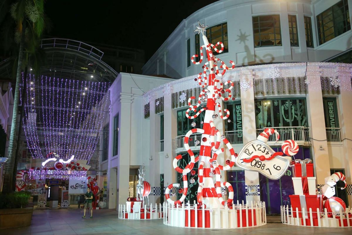 A boom lift is used to hoist the upper trunk section of the candy cane themed tree at Bugis Square.