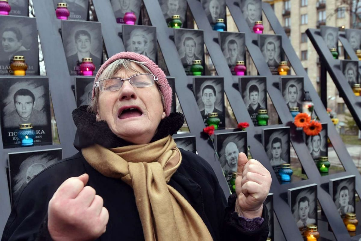 An elderly woman cries at the memorial for the killed Maidan activists during a ceremony marking the third anniversary of the Euromaidan beginning in central Kiev on Nov 21, 2016.
