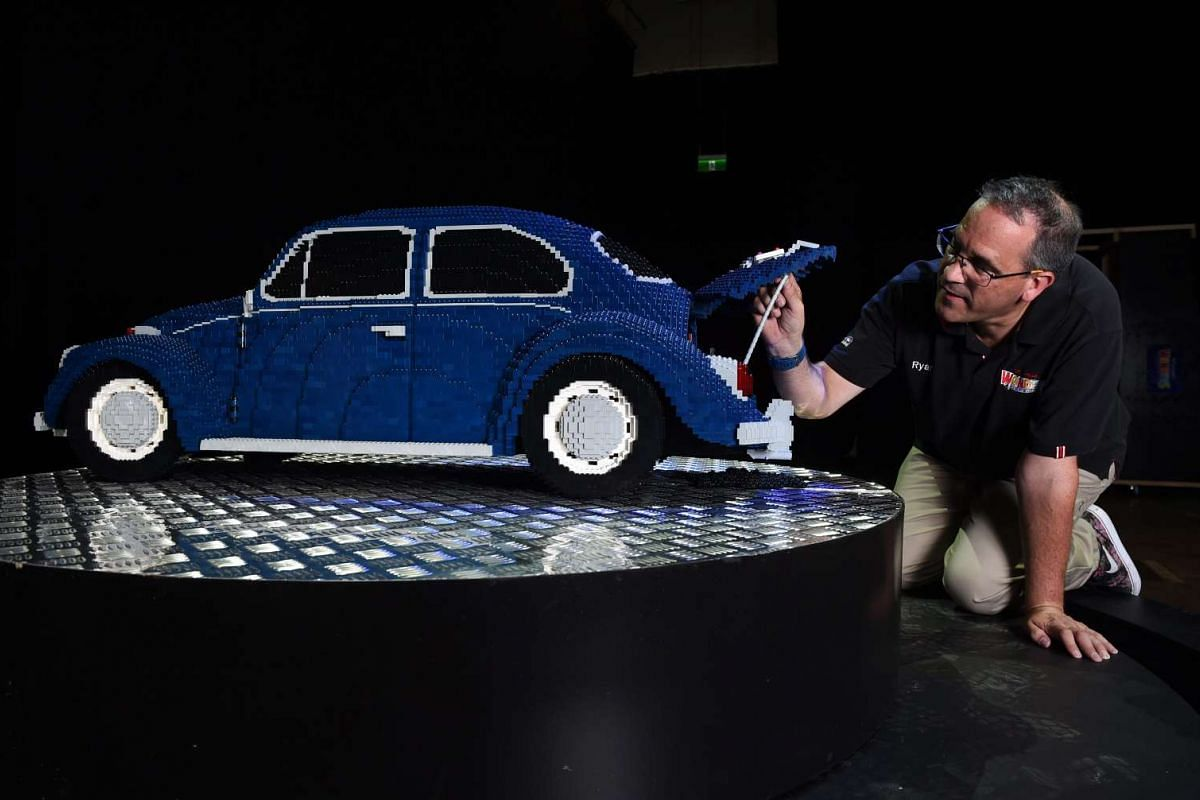 Lego Certified professional Ryan 'The Brickman' McNaught puts the finishing touches on a Lego model of a VW Beetle in Brisbane, Australia, on Nov 22, 2016.